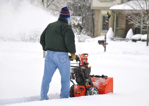 Mann mit Schneefräse in Vorgarten