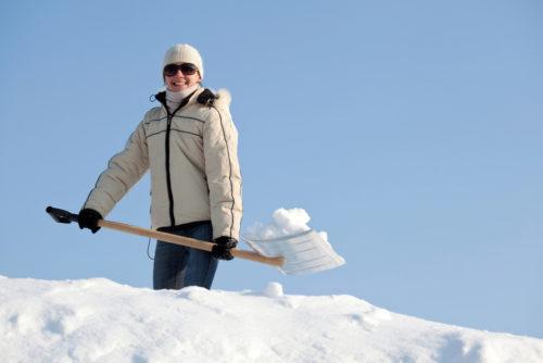 Frau mit Schneeschaufel